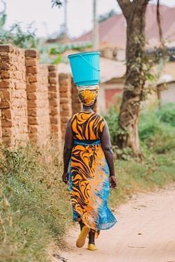 Konzept der Faszientherapie Rolfing - Schwerkraft verdeutlicht durch den geschmeidigen Gang einer afrikanischen Frau mit einer Last auf dem Kopf