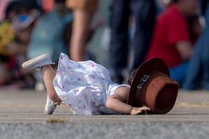 Kleines Mädchen kann wegen eines großen Hutes nicht sehen und stürzt auf die Hände 3