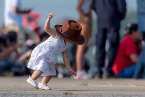 Kleines Mädchen kann wegen eines großen Hutes nicht sehen und stürzt auf die Hände 1