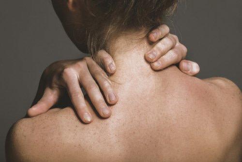Junge Frau mit Beschwerden - Faszientherapie kann an Ansatz sein