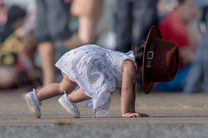 Kleines Mädchen kann wegen eines großen Hutes nicht sehen und stürzt auf die Hände 2