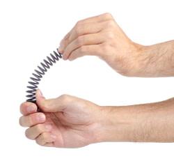 Stahlfeder zwischen 2 Händen die flexibel gespannt wird. Diese Spannung nutzen Sportler, um ihre Bewegungseffizienz zu vergrößern.