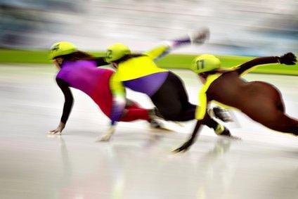 Eisschnellläufer im Rennen in einer Kurve. Sie zeigen wie Kufen auf Eis gleiten, sowie auch Faszien gleiten sollen.