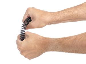 Hände pressen gewaltsam eine Stahlfeder zusammen