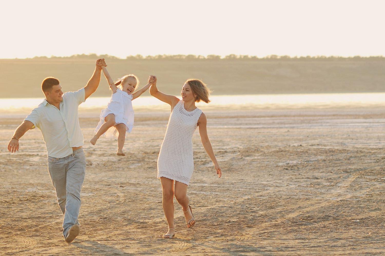 Elternpaar lässt ihre Tochter an hochgehobenen Armen durch die Luft fliegen.