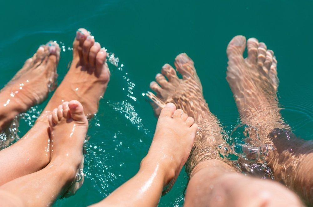 bewegliche Füße einer Familie im Wasser