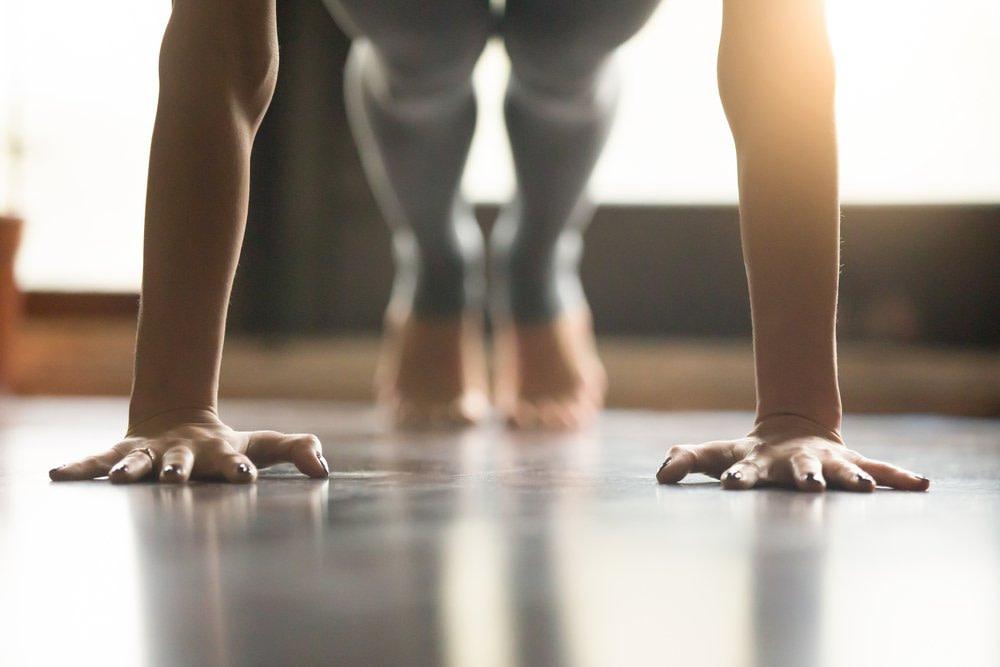 Hände einer jungen Frau in einer Yogaübung. Ihre Hände zeigen eine hohe Vorspannung, die Ihre Hatung unterstützt. Faszientherapie Rolfing Effizienz Vorspannung
