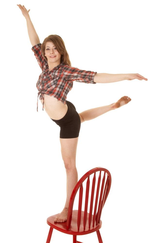 Junge Frau mit Raumorientierung auf einem Stuhl balancierend