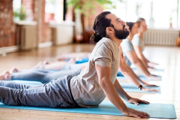 Rolfing Blick auf die Yoga PositionCobra - junger Mann in Yoga mit dem inneren Kampf der Öffnung im tiefen Hals Position die