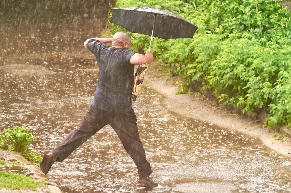 Mann springt mit hochgezogenen Schultern über eine Pfütze. Wenn dies ein Haltungsmuster widerspiegelt, wird er sich früher oder später in Behandung wegen Schulterschmerzen befinden
