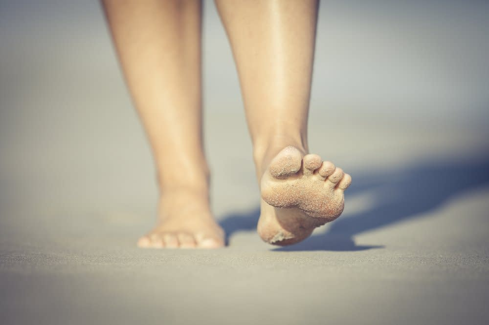Barfuß im Sand, wir sollten wie die junge Frau im Bild mit der Ferse aufkommen.