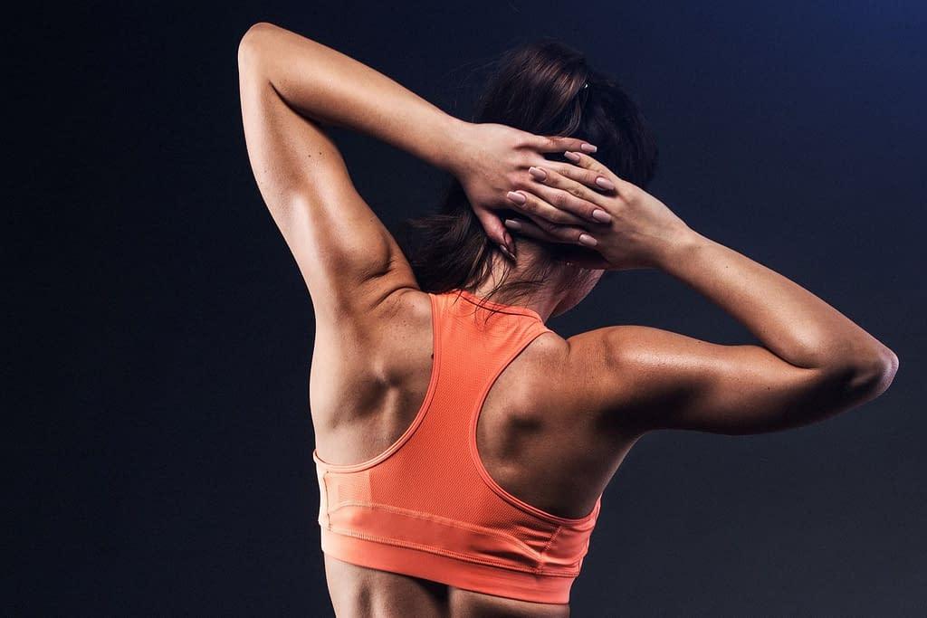 Verspannung in der Schulter, Rückenansicht einer trainierten Frau