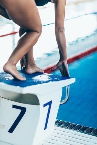 Schwimmerin auf einem Startblock in gespannter Haltung zum Sprung bereit
