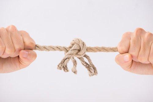 2 Händer ziehen eine Knoten stramm. Gleicher Muskeltonus unterbindet Bewegung.