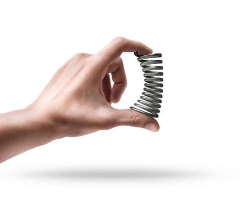 Hand dürckt eine Stahlfeder zusammen und zeigt was eine Vorspannung bedeutet. Die Faszientherapie Rolfing arbeitet im Körper mit dieser Vorspannung.