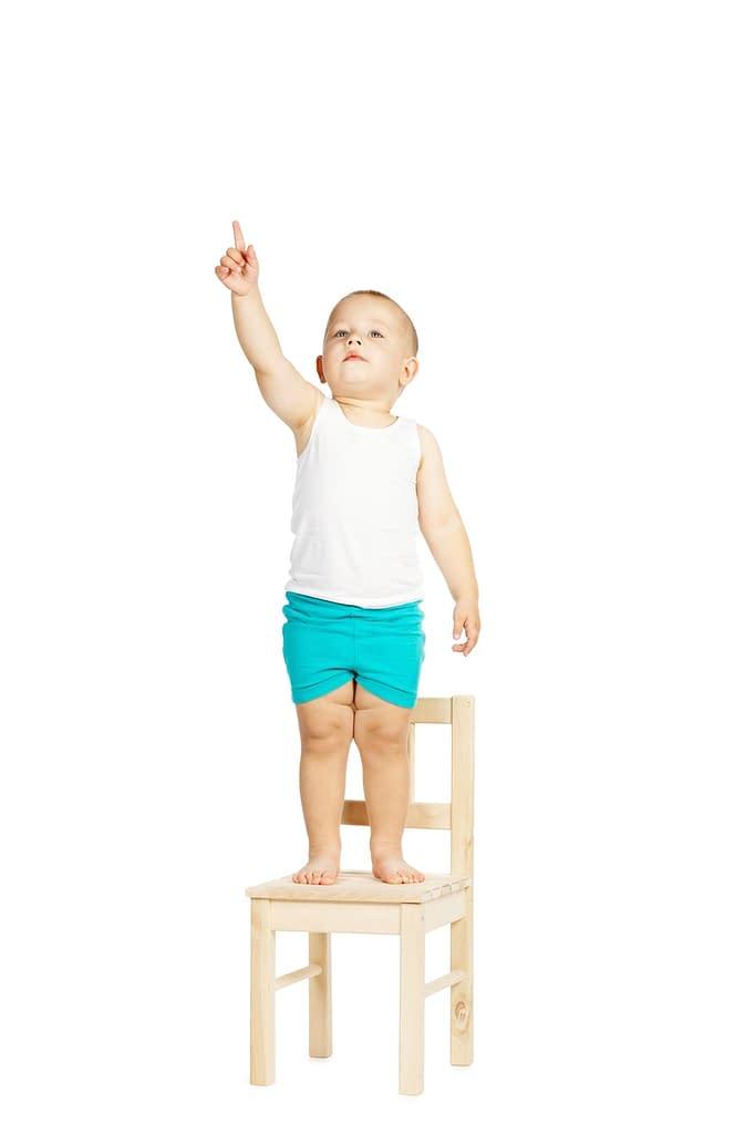 kleiner Junge auf einem Stuhl mit Bodenorientierung